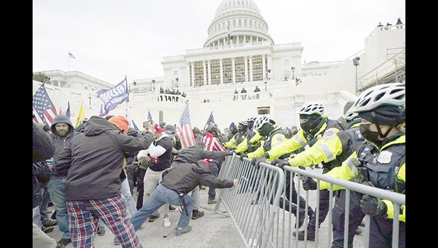 Trump supporters try to break through a police barrie