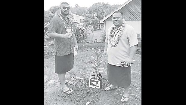 AS-EPA deputy director William Sili and AS-EPA finance and special projects manager, Victor Tuiasosopo next to a plant with a photo of the American Samoa flag.