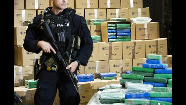 An officer stand guard over a fraction of the cocaine seized