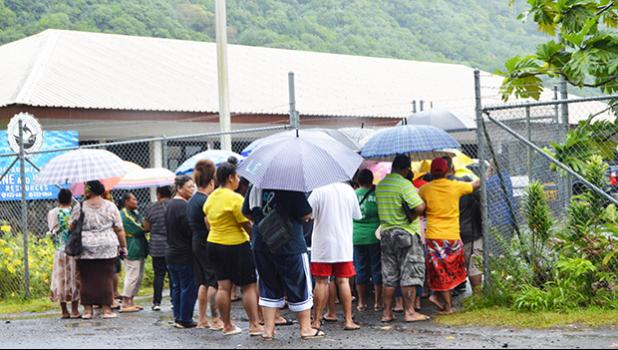 Crowd with umbrellas waiting at DMWR gate