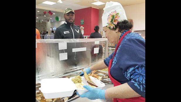 Congresswoman Aumua Amata dishing up food for troops