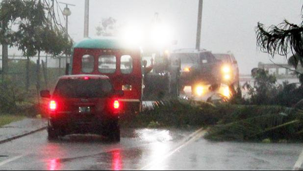 Emergency crews rushed to the scene a large downws tree in Fagaalu around 7a.m. Friday to clear the road as well as move an aiga bus, which was hit on the front section when the tree fell in the midst of strong gust winds from Tropical Storm Gati. No one was injured.  [photo: Fili Sagapolutele]