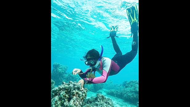 Molina swimming over a reef in snorkle gear