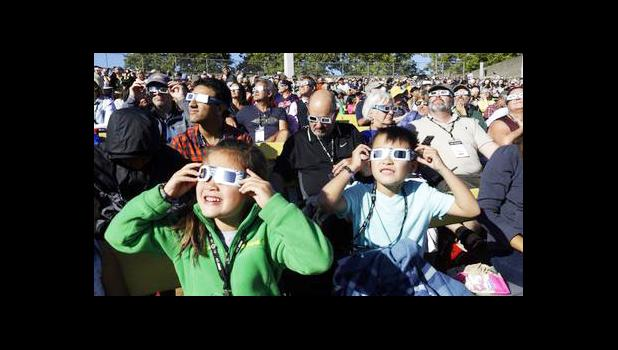 A crowd wears protective glasses as they watch the beginning of the solar eclipse from Salem, Ore., Monday, Aug. 21, 2017. (AP Photo/Don Ryan)