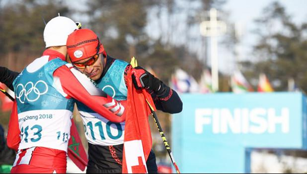 Morocco's Samir Azzimani (L) congratulates Tonga's Pita Taufatofua after he crossed the finish line during the men's 15km cross country freestyle at the Alpensia cross country ski centre during the Pyeongchang 2018 Winter Olympic Games on February 16, 2018 in Pyeongchang.  [AFP PHOTO / FRANCK FIFE vis RNZI]