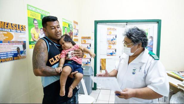 Nurse Fa'atafa Tavita (R) speaking with a father holding his child at the Apia Town Clinic in Samoa's capital city Apia.