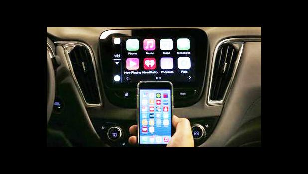 In this May 26, 2015 file photo, an iPhone is connected to a 2016 Chevrolet Malibu equipped with Apple CarPlay apps, displayed on the car's MyLink screen, top, during a demonstration in Detroit. The rapidly evolving in-car infotainment and navigation systems can be bewildering for all but the most tech-savvy car buyers. The average vehicle on U.S. roads is 11 years old; that means many people last went car shopping before iPhones were invented. (AP Photo/Paul Sancya)