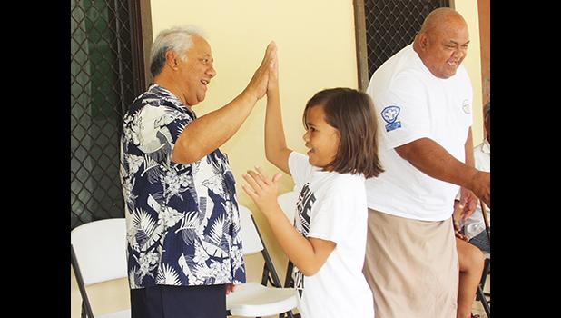FFAS president, Sen. Faiivae Iuli Alex Godinet, high fives a player on