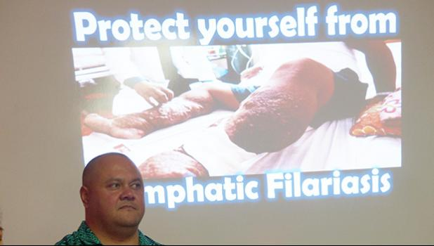 A Health Department official standing in front of a screen — in the background — showing a photo of a person affected with Lymphatic Filariasis