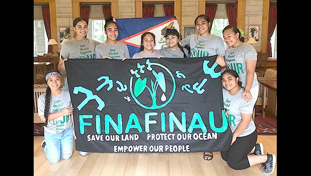Finafinau members with sign saying save our land, protect our ocean, empower our people