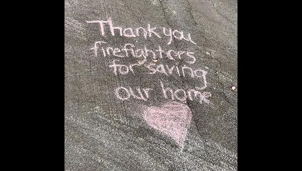 thank you message chalked on the driveway of a home that was spared.