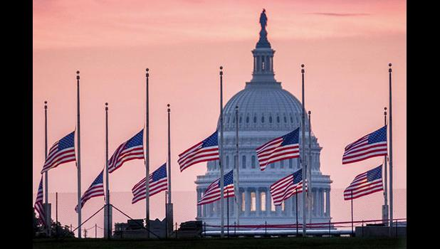 U.S. Capital building with flags at half staff