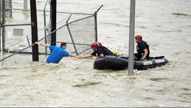 Rescue personnel grab the the hand of a man stranded in rushing water