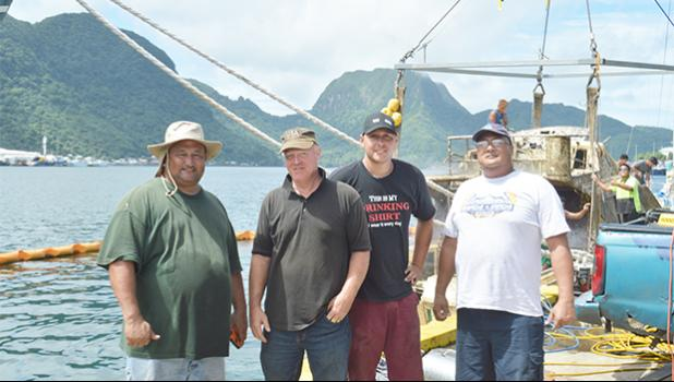 The two local businessmen who worked together to pull up the sunken Fo'isia vessel yesterday at the Malaloa Marina: (l-r) Iupeli Kava and Timothy Jones Sr., together with Timothy Jones Jr., and a bystander. The government owned Fo'isia sank - for reasons unknown - earlier this year in May. [photo: AF]