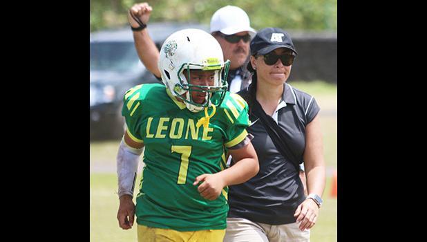 ASHSAA ATC Florence Wasko helping injured Leone Lions quarterback Isaiah Elisara off