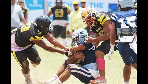 Charlie Toa Leama of Nu'uuli and a teammate sack Samoana's quarterback Viliamu Tanielu
