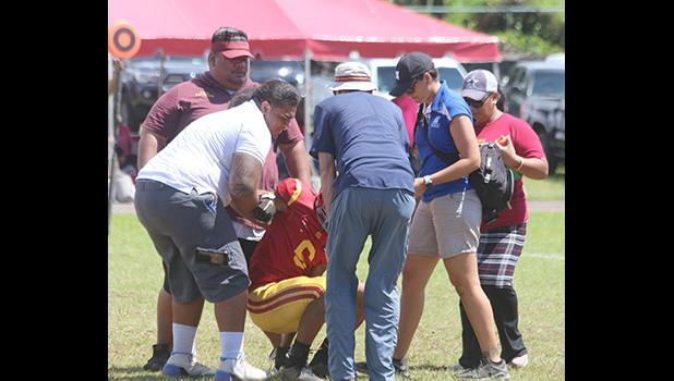 ASHSAA ATC Florence Wasko and Dr. Edwards helping Tafuna Warriors wide receiver Isaiah Gurr