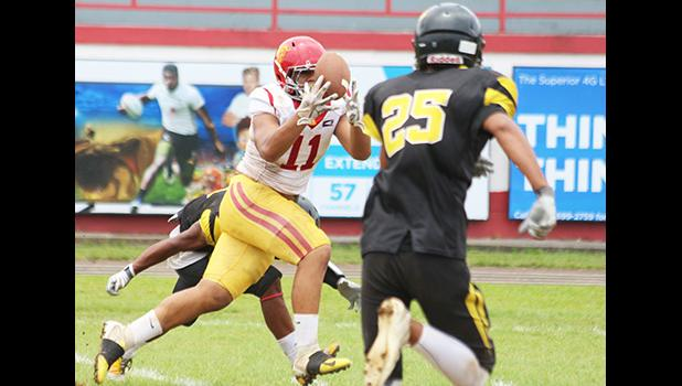 Herman Sufia (11) of the Tafuna Warriors focusing on catching this perfectly placed pass by Salave'a