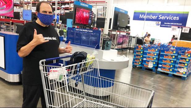Frank De Lima pushing a shopping cart and giving shaka sign