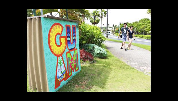 In this May 15, 2017, file photo, tourists walk through a shopping district in Tamuning, Guam. Security and defense officials on Guam said on Aug. 9, 2017, that there is no imminent threat to people there or in the Northern Mariana Islands after North Korea said it was examining its operational plans for attack. (AP Photo/Haven Daley, File)