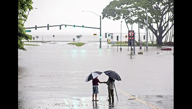 People stand near flood waters from Hurricane Lane in Hilo, Hawaii.