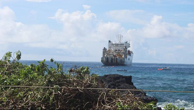 This Samoa News photo on Saturday morning, Apr. 21, 2018, shows the vessel, CS Responder, laying the undersea fiber optical cable for Hawaiki Submarine Cable LP, anchored off Fogagogo. Crew on two small boats are seen on the ocean, as VIPs and guests gathered on Fogagogo the high rocky shoreline area - close to the airport runway - to witness the Hawaiki cable landing.  [photo: FS]