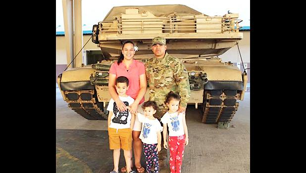 DeAngelo Herrera and family posing in front of a tank