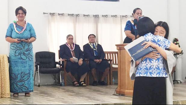 Manumalo Academy's Class of 2017 valedictorian Alice Park hugging her mom after receiving her diploma last Friday morning, while DOE Director Dr. Ruth Matagi-Tofiga, Pastor Filifaatali Mike Fuiava, and Paster Lemmy Seumanu look on. [photo: BC]