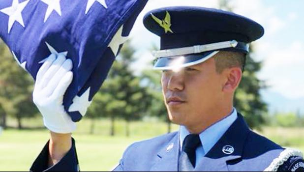 Senior Airman Darias Faaita preparing to present an American Flag to its recipient.