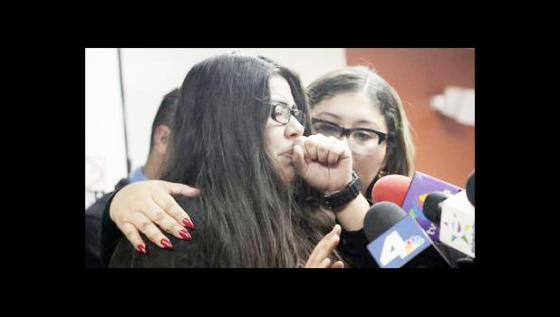 Marlene Mosqueda, left, who's father was arrested by ICE early Friday morning to be deported, is comforted at a news conference by her attorney Karla Navarrette at The Coalition for Humane Immigrant Rights of Los Angeles (CHIRLA) on Friday, Feb. 10, 2017. Navarrete, said she sought to stop Mosqueda from being placed on a bus to Mexico and was told by ICE that things had changed. She said another lawyer filed federal court papers to halt his removal. (AP Photo/Nick Ut)