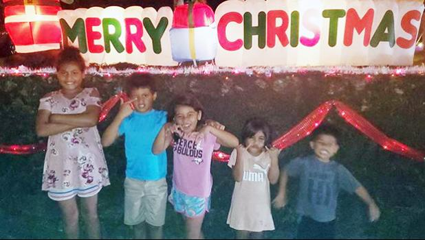 The Uelese siblings in front of a Merry Christmas display in Aoloau