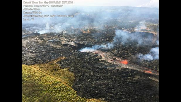 In this Sunday, May 20, 2018, aerial photo provided by the U.S. Geological Survey, lava from the eastern channel of the Fissure 20 complex flows into a crack in the ground in Pahoa, Hawaii. Kilauea volcano began erupting more than two weeks ago and has burned dozens of homes, forced people to flee and shot up plumes of steam from its summit that led officials to distribute face masks to protect against ash particles. (U.S. Geological Survey via AP)