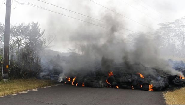 Lava crosses the road near Pohoiki Road, Friday, May 18, 2018, near Pahoa, Hawaii. Several open fissure vents are still producing lava splatter and flow in evacuated areas. Gas is also pouring from the vents, cloaking homes and trees in smoke. (AP Photo/Marco Garcia)