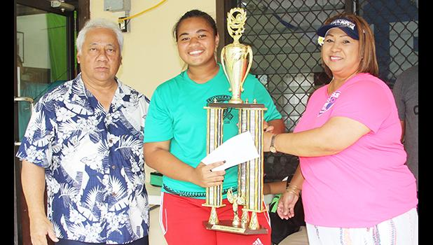 Pisita Lui of Lion Heart's Girls 13-15 team receives the championship trophy