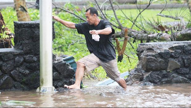 A man in Fagaalu navigating a flooded sidewalk area last week Friday — a typical sight during the aftermath of Tropical Storm Gita that hit the territory last Friday, followed up by a monsoon trough that dumped buckets of rain with high winds throughout the weekend.  [photo: TG]