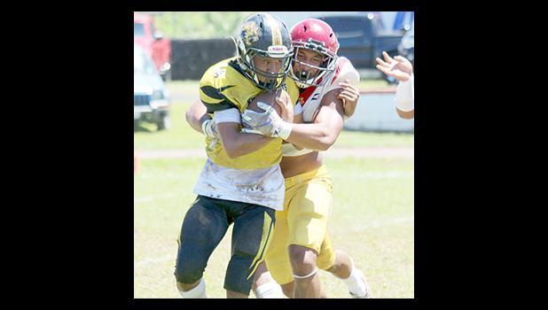 Tafuna Warriors Francisco Mauigoa and a Nuuuli Wildcat ball carrier