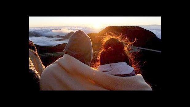 A couple watches as the sun rises in front of the summit of Haleakala volcano in Haleakala National Park on Hawaii's island of Maui, Sunday, Jan. 22, 2017. Sunrise viewing has long been popular at Haleakala, one of the main attractions at Haleakala National Park despite morning temperatures that often dip into the 30s. (AP Photo/Caleb Jones)