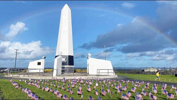 Small American Flags in front of Veterans Memorial Monument with rainbow overhead