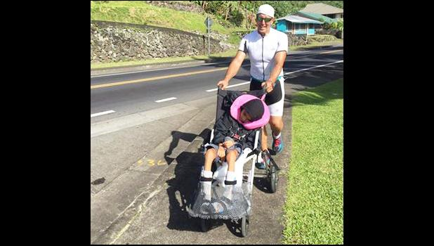 Matt Bracken, who took home second place during Saturday's Triathlon Olympic Division, is seen pushing Miracle, one of the Special Olympians on a stroller during the running portion of the competition.  [photo: Mark Espiritu]