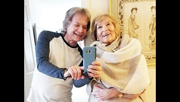 Leland Stein, left, takes a photo with his mother Sondra Green