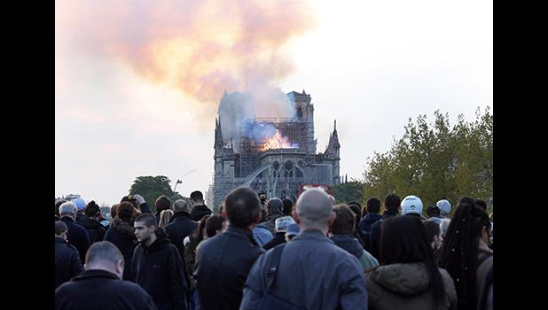 In this Monday, April 15, 2019 file photo, people watch as flames and smoke rise from Notre Dame cathedral