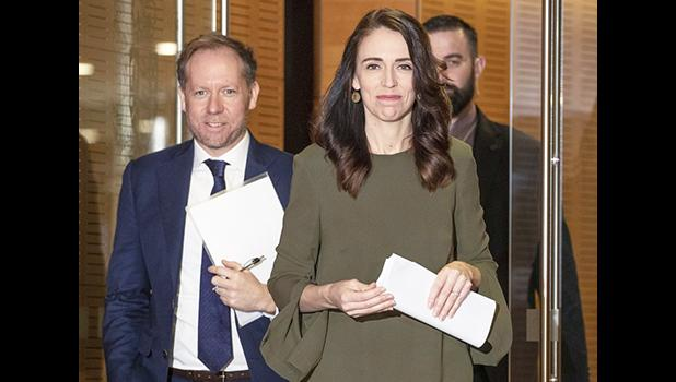 New Zealand Prime Minister Jacinda Ardern with two men in the background
