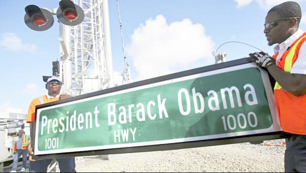 "In this Thursday, Dec. 17, 2015 file photo, Dale Moncur, left, and Cedric Anderson of Palm Beach County Traffic Operations, hold a sign for the new President Barack Obama Highway in preparation to change it from the ""Old Dixie Highway"" in Riviera Beach, Fla. On Friday, Jan. 5, 2018, The Associated Press reported that stories circulating on the internet about President Donald Trump ordering the name of the highway changed back to ""Old Dixie"" are untrue. (Lannis Waters/Palm Beach Post via AP)"