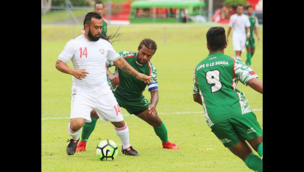 Suliasi Lauhoua (14) of Veitongo FC trying to defend against Michael Fifi'i of Lupe ole Soaga during the opening half of their match up last Friday afternoon. Veitongo FC lost 6 - 0 against the Samoans. [photo: TG]