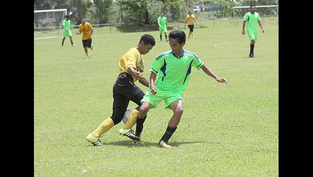 A Pago Youth players tries to dribble away from a Taputimu player