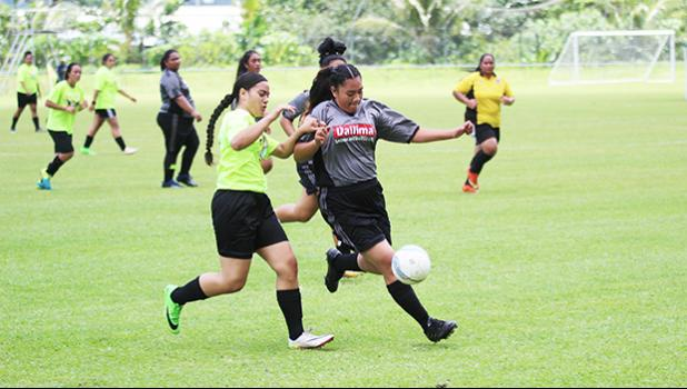 A Pago Youth player challenges a Taputimu Youth defender