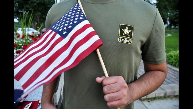 a Pakistani recruit, 22, who was recently discharged from the U.S. Army, holds an American flag as he poses for a picture. The man asked his name and location to be undisclosed for safety reasons. The AP interviewed three recruits from Brazil, Pakistan and Iran, all of whom said they were devastated by their unexpected discharges