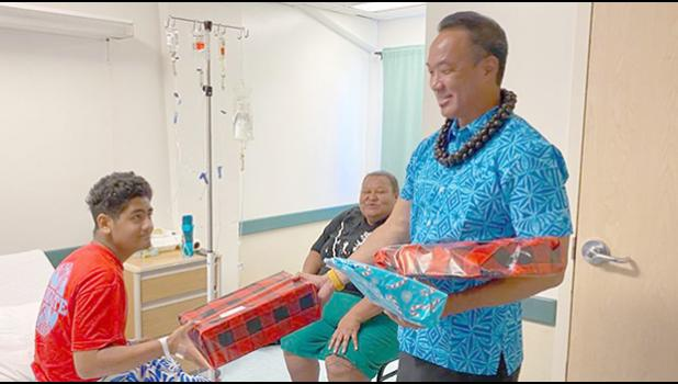 A young man named Troy receives a gift from Paul Young on behalf of Rotary Club of Pago Pago