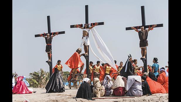Ruben Enaje, center, dressed as Jesus, is seen nailed on cross