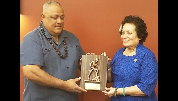 """Robert """"Koko"""" Yandall, retired Chief Warrant Officer 5, from Leone Village, presents Amata with a plaque from the Soldiers and Veteran Retirees at Fort Bragg. [courtesy photo]"""